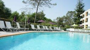 Una piscina al aire libre, tumbonas