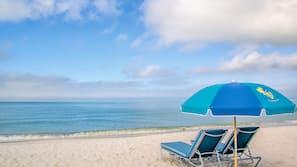 Aan het strand, wit zand, ligstoelen aan het strand, parasols
