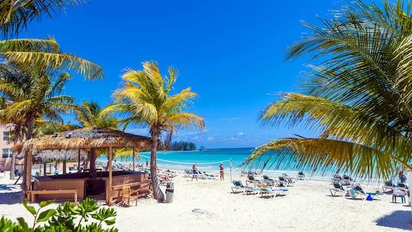 Praia particular, areia branca, espreguiçadeiras