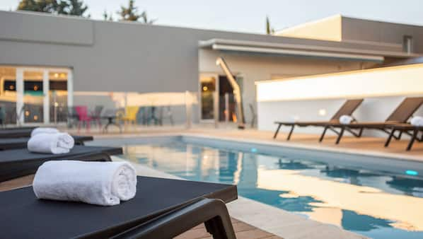 Seasonal outdoor pool, open 9:00 AM to 9:00 PM, pool loungers