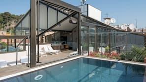 Een buitenzwembad, ligstoelen bij het zwembad