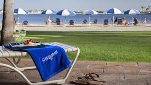 Sulla spiaggia, sabbia bianca, cabine (a pagamento), lettini da mare