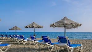 Am Strand, schwarzer Sandstrand, Liegestühle