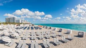 On the beach, white sand, beach cabanas, sun-loungers