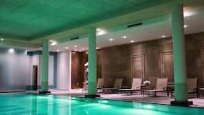 Een binnenzwembad en ligstoelen