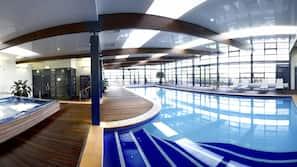 Una piscina cubierta, tumbonas
