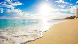 Praia particular, areia branca, espreguiçadeiras, toalhas de praia