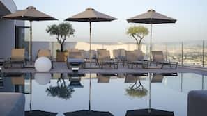 Una piscina al aire libre, una piscina climatizada, sombrillas, tumbonas
