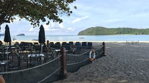 On the beach, sun-loungers, beach umbrellas, beach bar