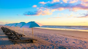 Rannalla, aurinkotuoleja, aurinkovarjoja, rantapyyhkeitä