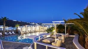 Een binnenzwembad, een buitenzwembad, parasols voor strand/zwembad