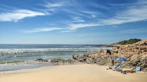 In Strandnähe, weißer Sandstrand, Sonnenschirme, Strandtücher