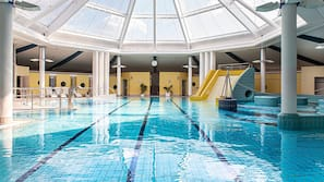 Een binnenzwembad, een buitenzwembad, ligstoelen bij het zwembad