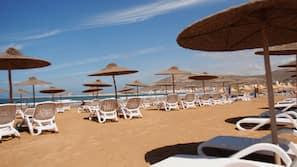 Ubicación cercana a la playa, tumbonas y sombrillas