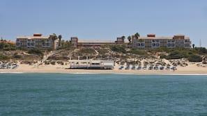 Ubicación a pie de playa, arena negra, tumbonas y sombrillas