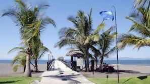 On the beach, black sand, beach umbrellas, beach towels