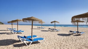 Am Strand, weißer Sandstrand, Strandtücher, Volleyball