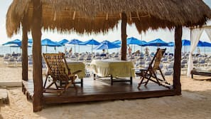 On the beach, white sand, sun loungers, beach umbrellas