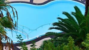 Een buitenzwembad en parasols bij het zwembad