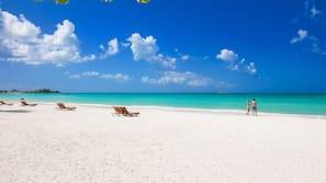 On the beach, white sand, beach cabanas, sun loungers