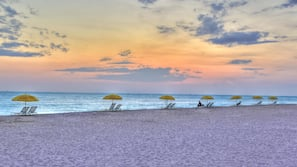 On the beach, white sand, beach cabanas, beach volleyball