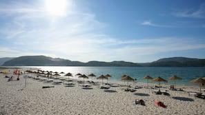 Aan het strand, wit zand, parasols, beachvolleybal
