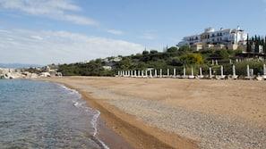 På stranden, solstolar, parasoller och strandbar
