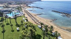 På stranden, solstolar, parasoller och vattenskidåkning