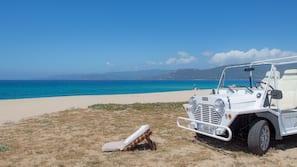 Vlak bij het strand, wit zand, parasols, strandlakens