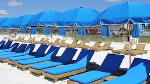 On the beach, white sand, beach cabanas, sun-loungers