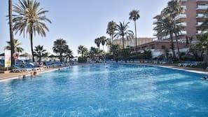 Een buitenzwembad, parasols bij het zwembad en ligstoelen