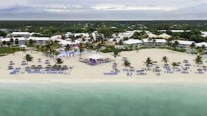 Na praia, areia branca, espreguiçadeiras, toalhas de praia