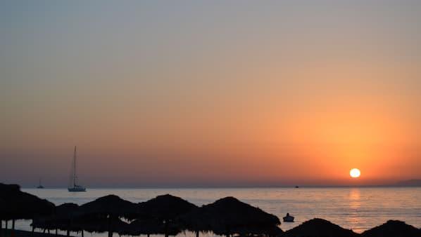 Am Strand, schwarzer Sandstrand, Liegestühle, Sonnenschirme