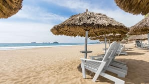 På stranden, hvit sand, solsenger og parasoller