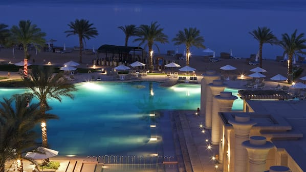 Una piscina cubierta, sombrillas, tumbonas