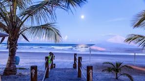 Na praia, espreguiçadeiras, guarda-sóis, toalhas de praia