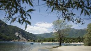 Een privéstrand, ligstoelen aan het strand, parasols, kajakken