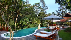 Outdoor pool, a natural pool, open 7 AM to 6 PM, pool umbrellas