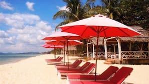 Een privéstrand, ligstoelen aan het strand