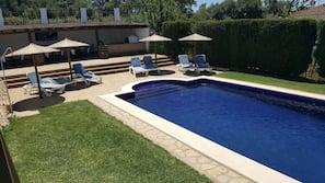 Una piscina al aire libre, una piscina con cascada, tumbonas