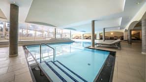 Een binnenzwembad, een buitenzwembad en parasols bij het zwembad