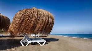 Een privéstrand, ligstoelen aan het strand, parasols, een strandbar