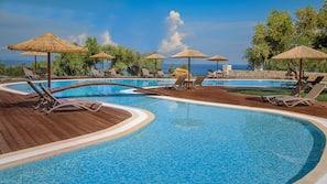 Outdoor pool, an infinity pool, pool umbrellas, sun loungers