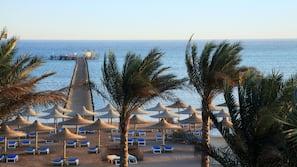 Een privéstrand, ligstoelen aan het strand, parasols, duiken