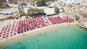 On the beach, sun-loungers, beach umbrellas, motor boating