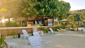 Plage privée, sable blanc, chaises longues, serviettes de plage