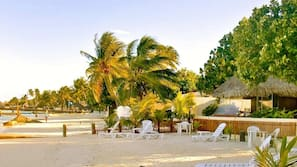 Aan een privéstrand, wit zand, ligstoelen, strandlakens
