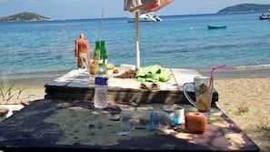 Nära stranden, solstolar, parasoller och strandbar