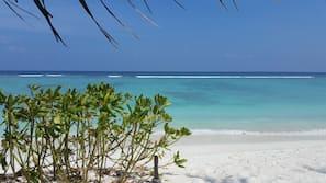 På stranden, hvit sand, solsenger og strandhåndklær