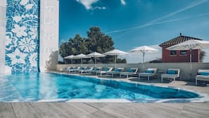Outdoor pool, a natural pool, open 10:00 AM to 7:00 PM, pool umbrellas
